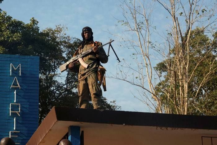 A CAR soldier stands on a roof while guarding Bambari town hall last month. The country's fourth-largest city was briefly seized by rebels this week