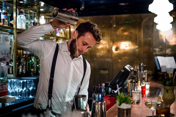 A young man makes a cocktail