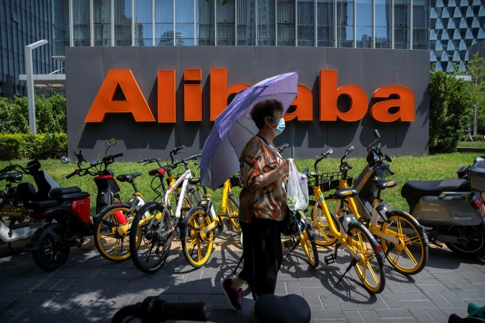 A woman holds an umbrella as she walks past the offices of Chinese ecommerce group Alibaba in Beijing