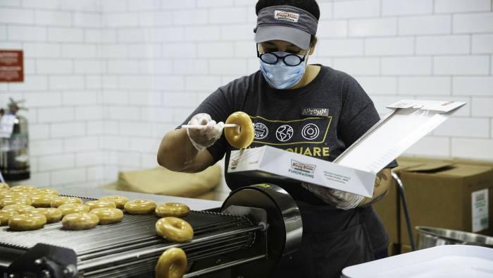 An employee wearing a protective mask boxes doughnuts inside a Krispy Kreme store