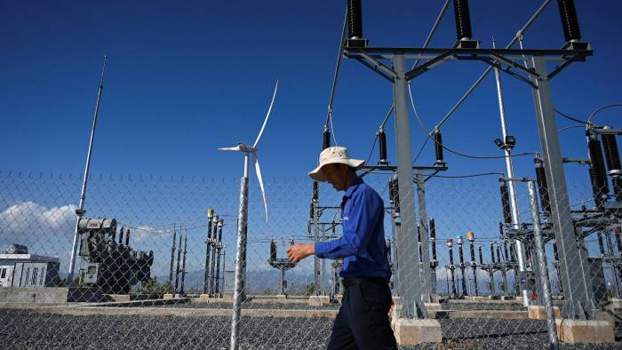 a man walking past power installations at the Phu Lac wind farm in southern Vietnam's Binh Thuan province