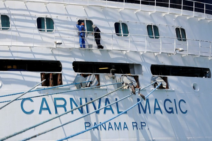 Workers perform maintenance on the Carnival Magic cruise ship while it is docked at Port Canaveral, Florida