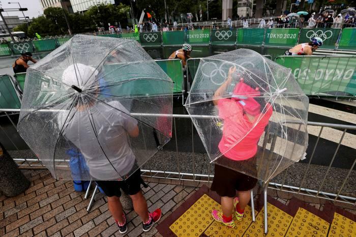 Fanoušci se snaží zahlédnout závody žen v triatlonu v dešti způsobeném tropickou bouří Nepartak