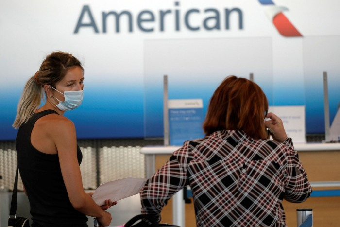 Travellers wear masks as they wait at an American Airlines ticket counter at O'Hare International Airport in Chicago