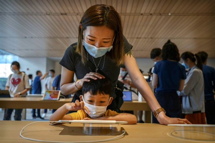 A mother and child try an iPad at an Apple store in the Sanlitun shopping area in Beijing, China
