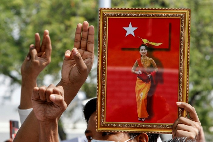 Myanmar citizens living in Thailand make the three-finger pro-democracy salute during a protest in February demanding the release of Aung San Suu Kyi