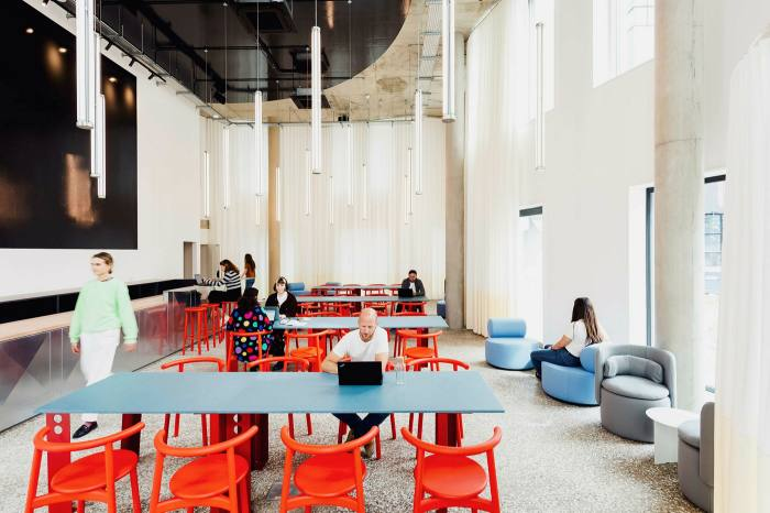An open-plan, high-ceilinged space with tables, chairs and sofas