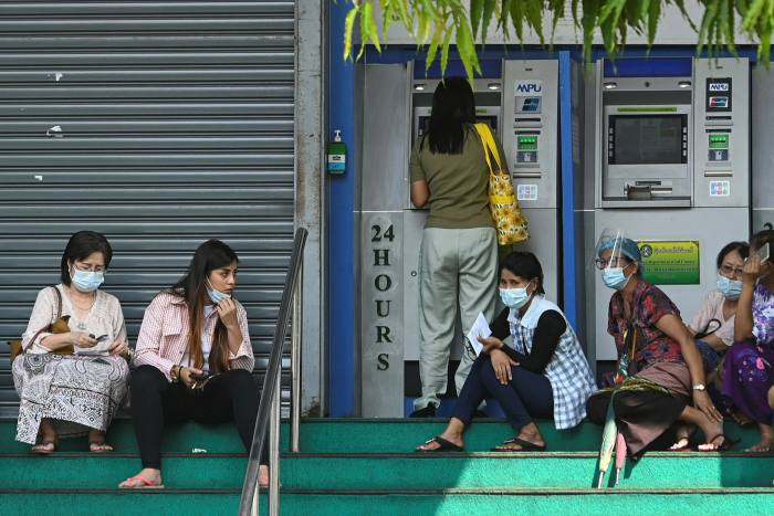 People wait to withdraw money from a Myawaddy Bank ATM in Yangon