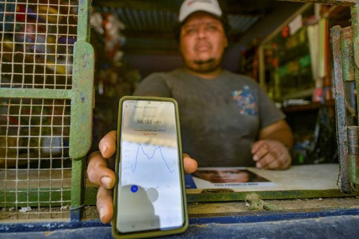 A man in El Salvador displays a phone app that shows the price of bitcoin