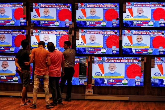 People watch PM Narendra Modi's speech on TV in March 2020 about India's response to the spread of coronavirus