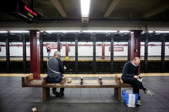 Commuters wait for a subway on the Pennsylvania Station platform in New York in June
