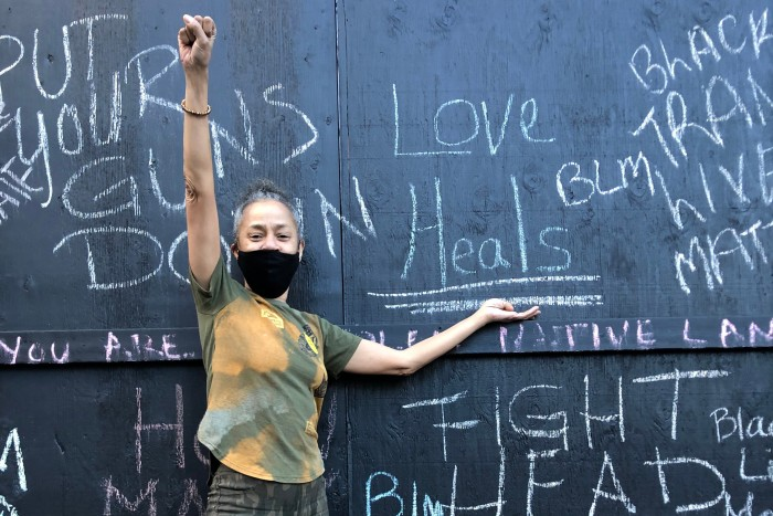 Pamela McClain points to her message on a board set up for protesters in Minneapolis