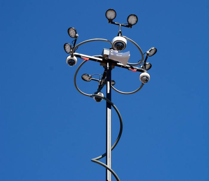 A piece of police surveillance equipment involving cameras, lights and a loud speaker mounted on a long pole