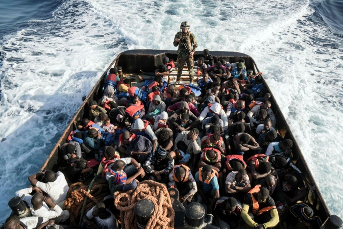 Migrants on an overcrowded boat off the coast of Libya. More than 700,000 migrants are currently stranded in Libya, according to the International Rescue Committee