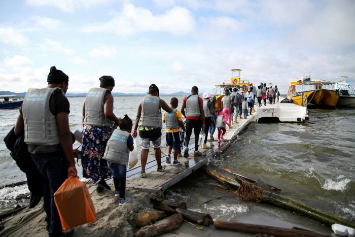 Migrants, mostly Haitians, board a boat bound for Acandi, Colombia to later cross into Panama and continue north.