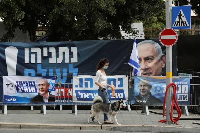 A women walks near posters supporting Israeli prime minister and leader of the Likud party Benjamin Netanyahu in Jerusalem, Israel