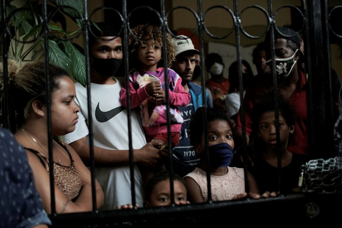 Squatters peer from behind the iron gate of a house that about 19 families have been occupying for close to a year, before being evicted, in Rio de Janeiro last September