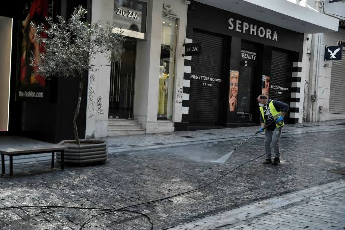 A street cleaner works in front of shuttered clothes shops in Athens. At a time when retailers would normally be placing orders for their Spring 2021 collections, they are instead trying to unpick contracts