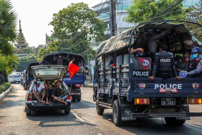 Demonstrators in a car sing protest songs as they pass a police truck