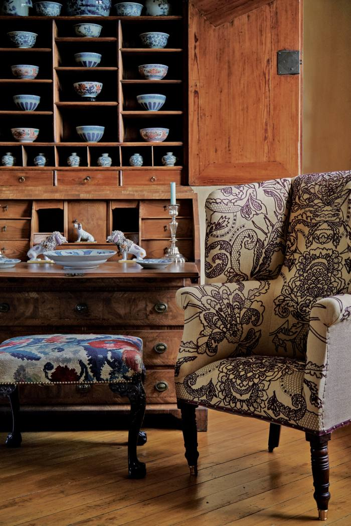 An antique wing chair reupholstered in embroidered linen designed by Copping and Rigaud (POA)