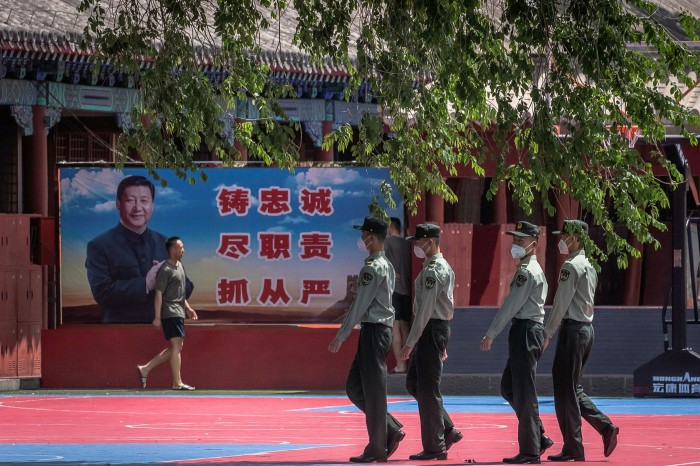 Chinese soldiers in Beijing march past a banner depicting Xi Jinping. After largely disappearing from view in late January, the president finally showed up on the front lines of the battle against coronavirus on February 10