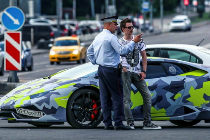 Maksim Yakubets speaks to a police officer in front of a fluorescent camouflage Lamborghini