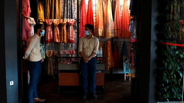 Shopkeepers wait for customers in a mall after the government eased a coronavirus lockdown in New Delhi, India.