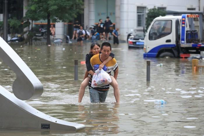 Un hombre lleva a una mujer a lo largo de una calle inundada después de que retrocedieran lluvias récord en la ciudad de Zhengzhou, en la provincia de Henan, en el centro de China