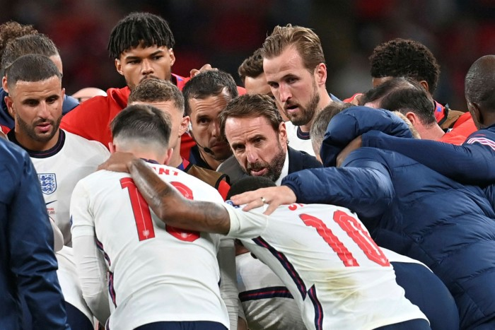England's coach Gareth Southgate speaks to his players ahead of extra time during the Euro 2020 semi-final match against Denmark at Wembley on Wednesday