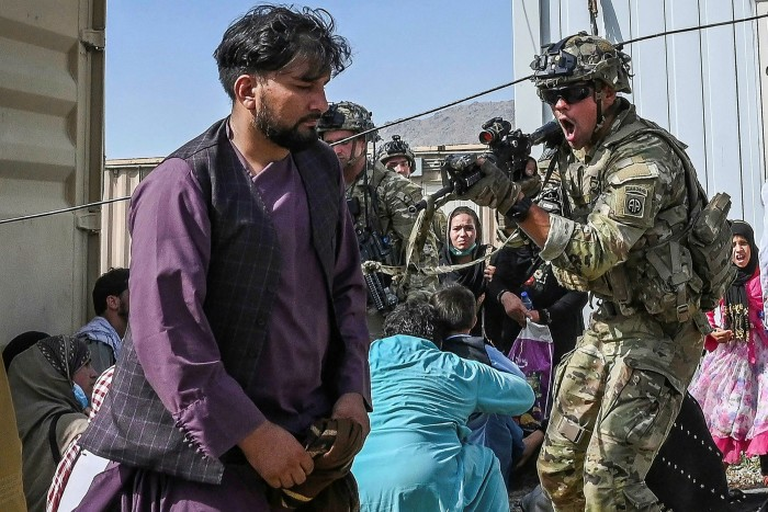 A US soldier points his gun at an Afghan passenger at Kabul airport on Monday as thousands of people mobbed the airport to flee the country