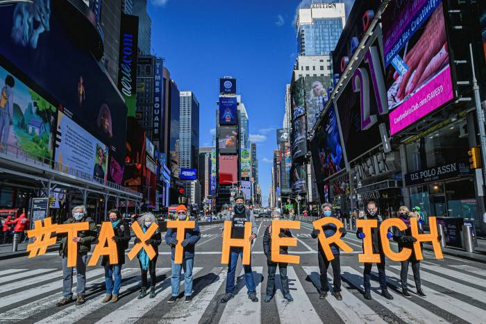 Participants seen spelling out #TaxTheRich at Times Square
