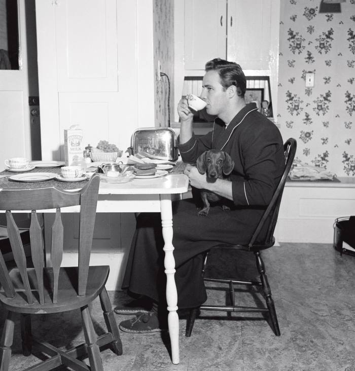Marlon Brando having breakfast in a dressing gown and slippers in 1949