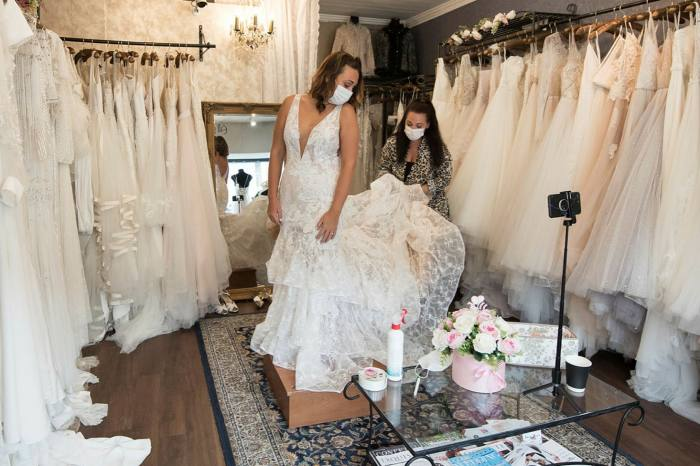 Future bride Sharni wears a face mask as she tries on wedding dresses in the Blush bridal boutique Leigh-on-Sea