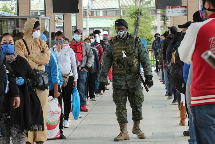 A soldier walks in between people lining up to take the bus  in Quito, Ecuador. The country  suffered a particularly horrific wave of infections in April