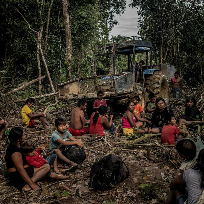 Members of the indigenous Munduruku tribe, on a trek to a mining camp, take a break in front of equipment used to illegally mine their land, in the Amazon rainforest in 2018