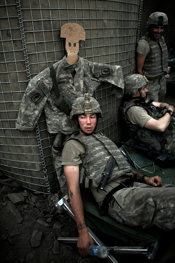 Soldiers sit with a dummy used to draw enemy fire at a Korengal Valley bunker in 2007