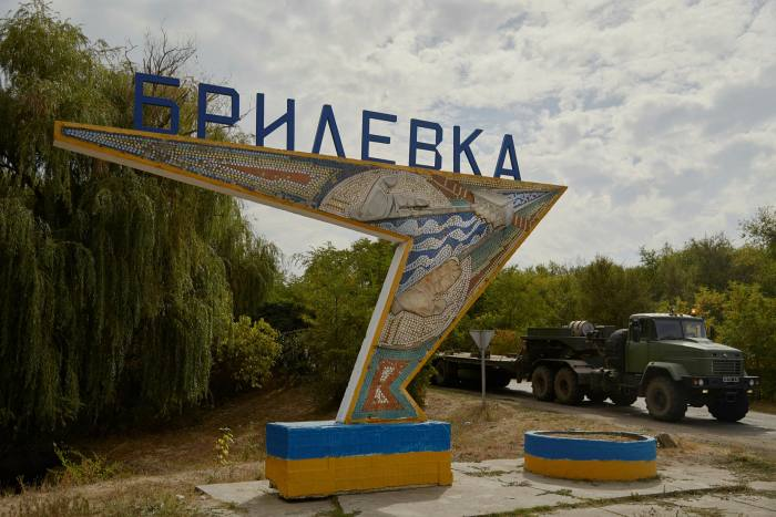 A Ukraine military vehicle drives past a Soviet monument marking the entrance to Brylivka