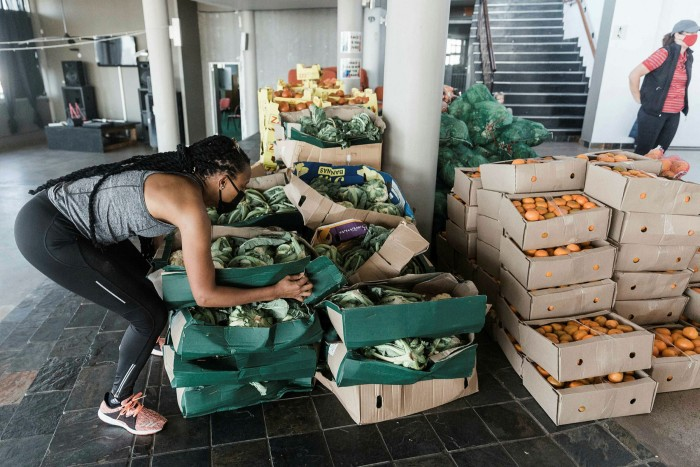 A woman stacks boxes of fresh fruits and vegetables