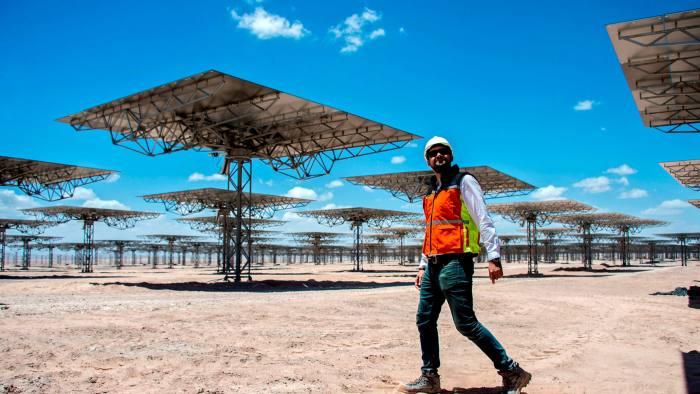 A worker walks near solar panels at Cerro Dominador, in Latin America