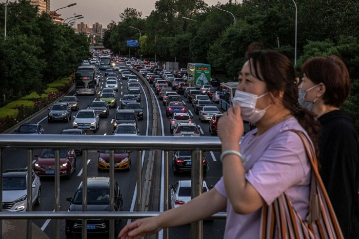Women wearing face masks cross over a road jammed with cars during rush hour in Beijing. Indications from China are of a sharp rise in individual car use
