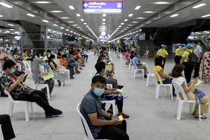People wait after receiving the Sinovac Biotech Covid-19 vaccine at a centre set up at the Bang Sue Grand Station in Bangkok on Monday