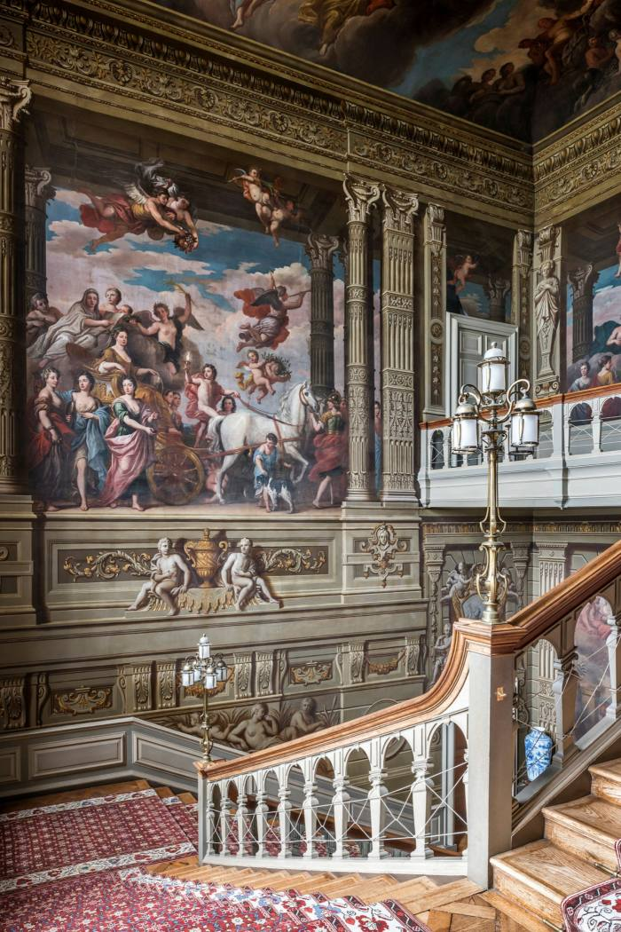 The Grand Staircase, with a view of Louis Laguerre's 1720 mural of the Duchess of Somerset riding in triumph through the grounds of Petworth House
