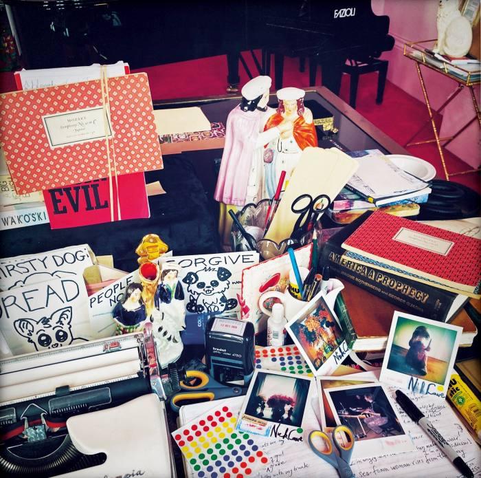 Cave's desk, with Polaroids, £100 each, andDread tiles, £20 each