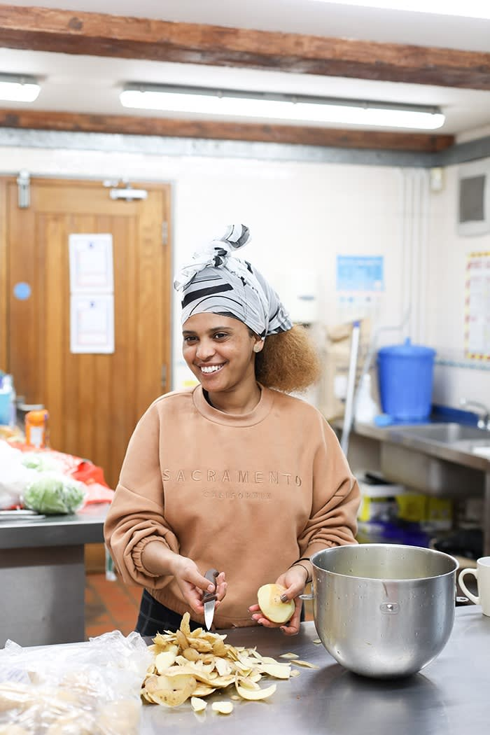 Ruta Yemane, smiling, peels potatoes in the Herd Farm kitchen