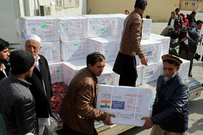 Afghan health ministry workers unload boxes of the first shipment of 500,000 doses of the AstraZeneca vaccine made by Serum Institute of India