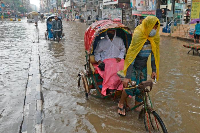 Rickshaw pullers make their way through a water-logged street after a heavy downpour in Dhaka on July 21, 2020