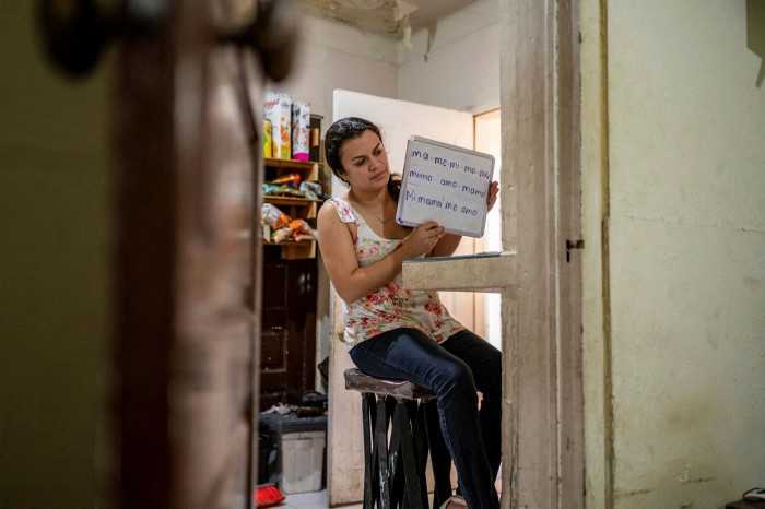 Teachers carry a whiteboard to study at their home in Matamoros, Mexico