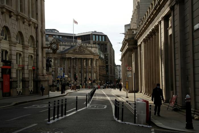 People walk past the Bank of England in the City of London