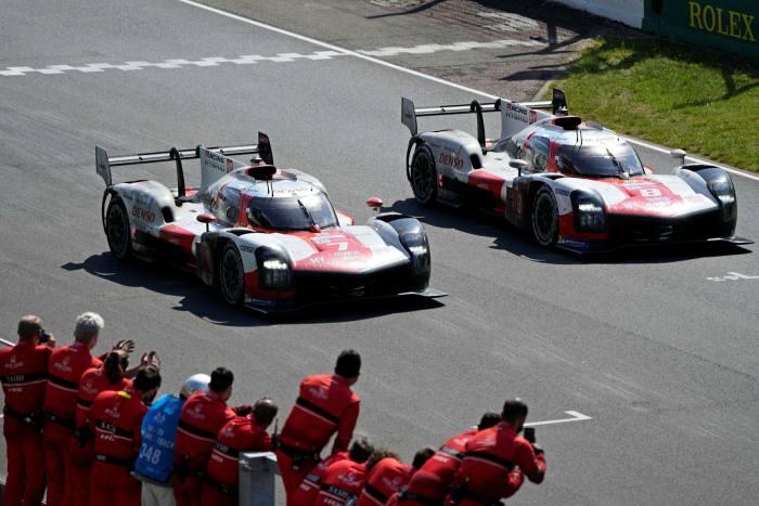 Mechanics cheer as Kamui Kobayashi of Japan, left, driving Toyota Gazoo Racing's Toyota GR010 Hybrid (7) crosses the finish line to win the 24-hour Le Mans endurance race on Sunday