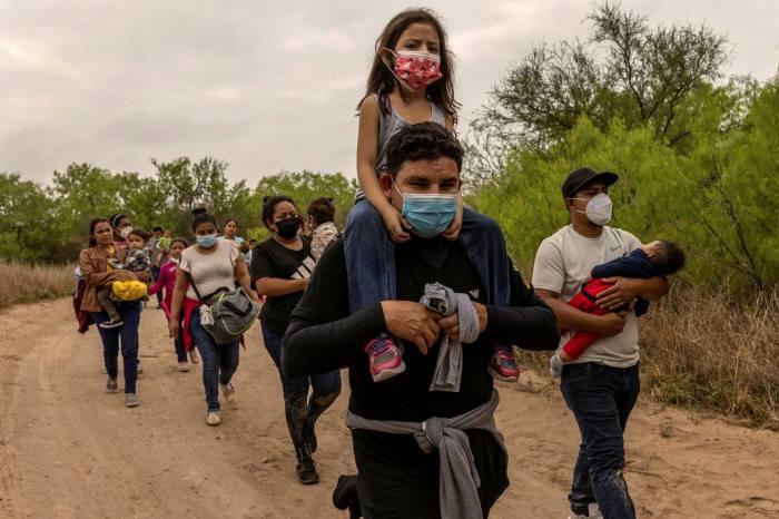 Migrants walk towards a US border Patrol checkpoint near Mission, Texas